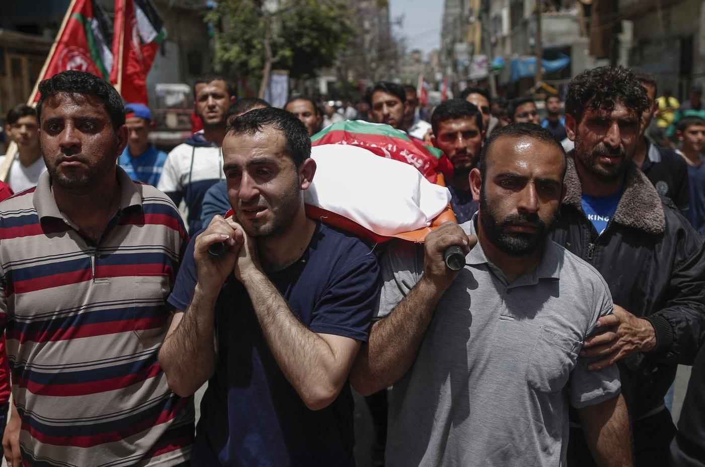 Relatives carry the body of a Palestinian, who was killed in Israeli strikes the previous day, during a funeral ceremony in Beit Lahia, in northern Gaza Strip (AFP)