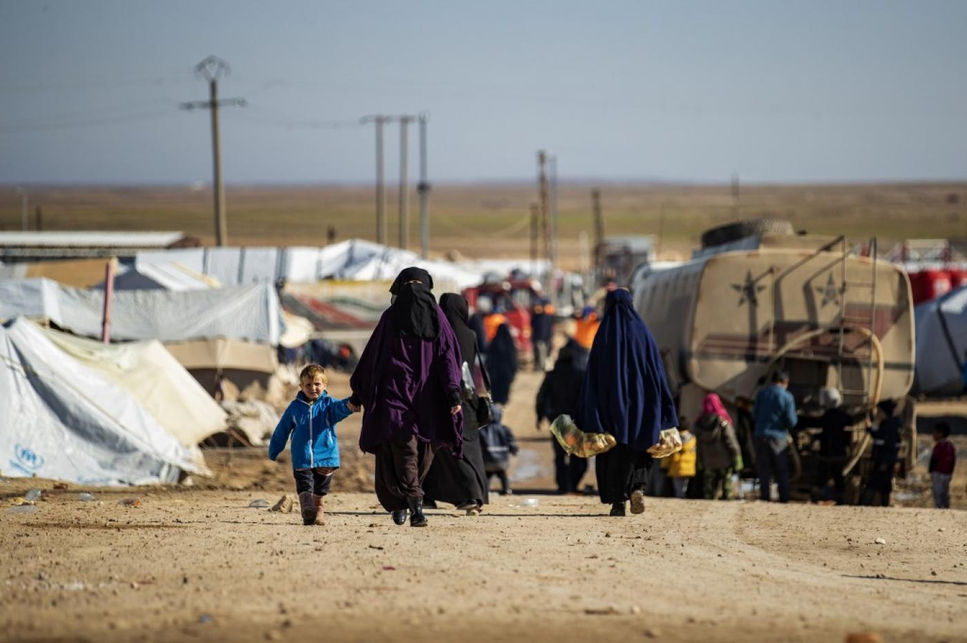 Women walk by with children in a main alley of the Kurdish-run al-Hol camp in Syria in January.