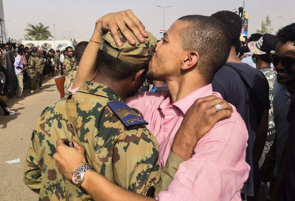 A Sudanese protester kisses a soldier on 11 April in Khartoum (AFP)