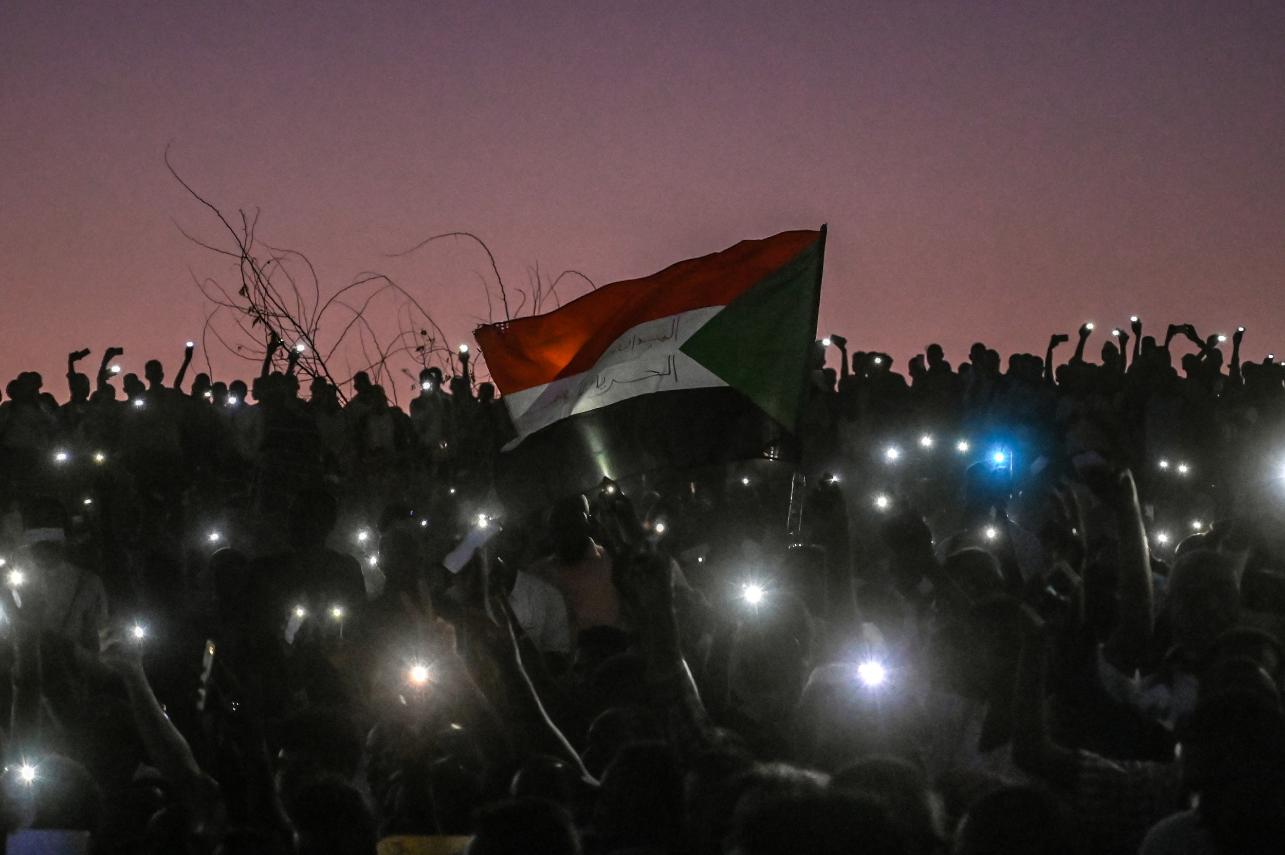 Sudanese protesters open their smartphones lights during a protest outside the army headquarters in the capital Khartoum on 21 April 2019 (AFP)