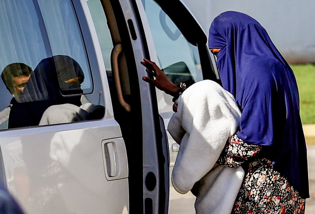 A Sudanese woman who allegedly belonged to IS is escorted into a vehicle in northeastern Syria after being handed over to Sudanese diplomats in September 2018 (AFP)