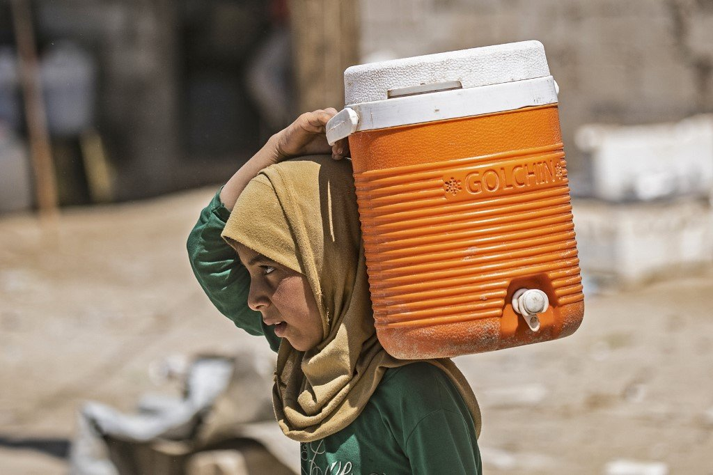 A displaced Syrian girl carries water on her shoulder in al-Hol camp on 18 April (AFP)
