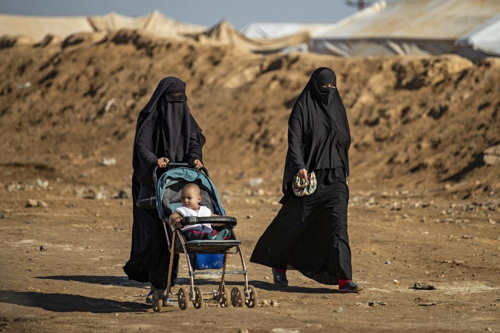 Syrian women walk through a camp in northeastern Syria on 14 January (AFP)