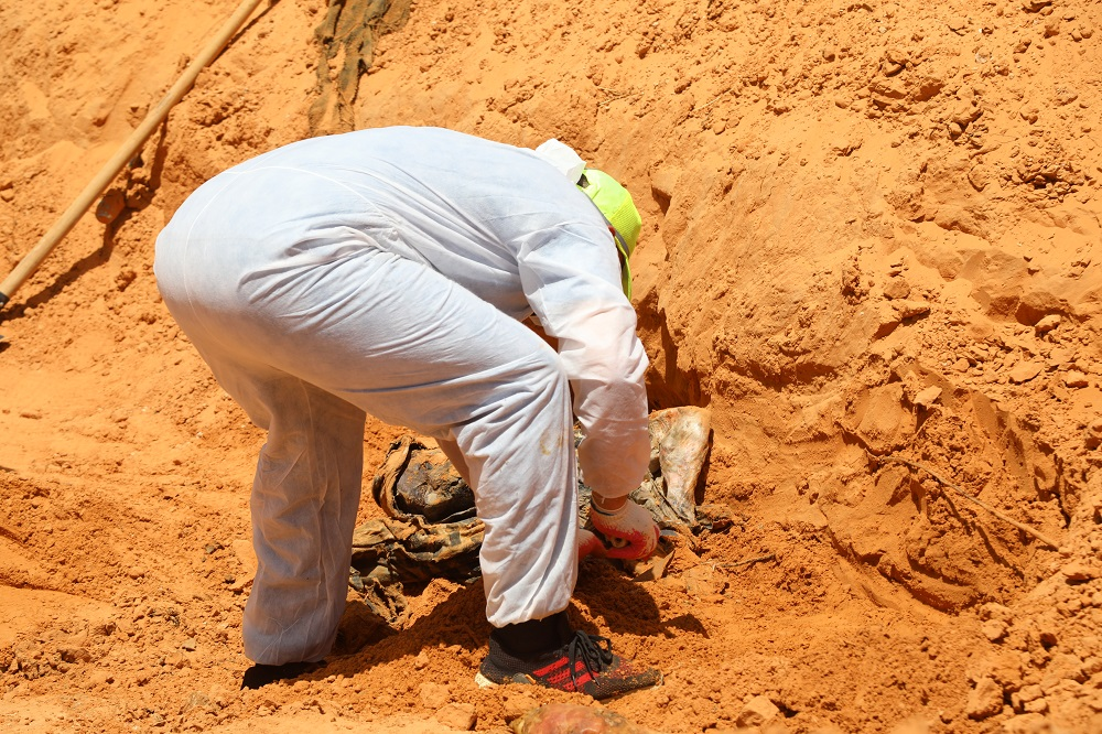 A body is uncovered at a mass grave site in Tarhuna on 10 June 2020 (MEE)