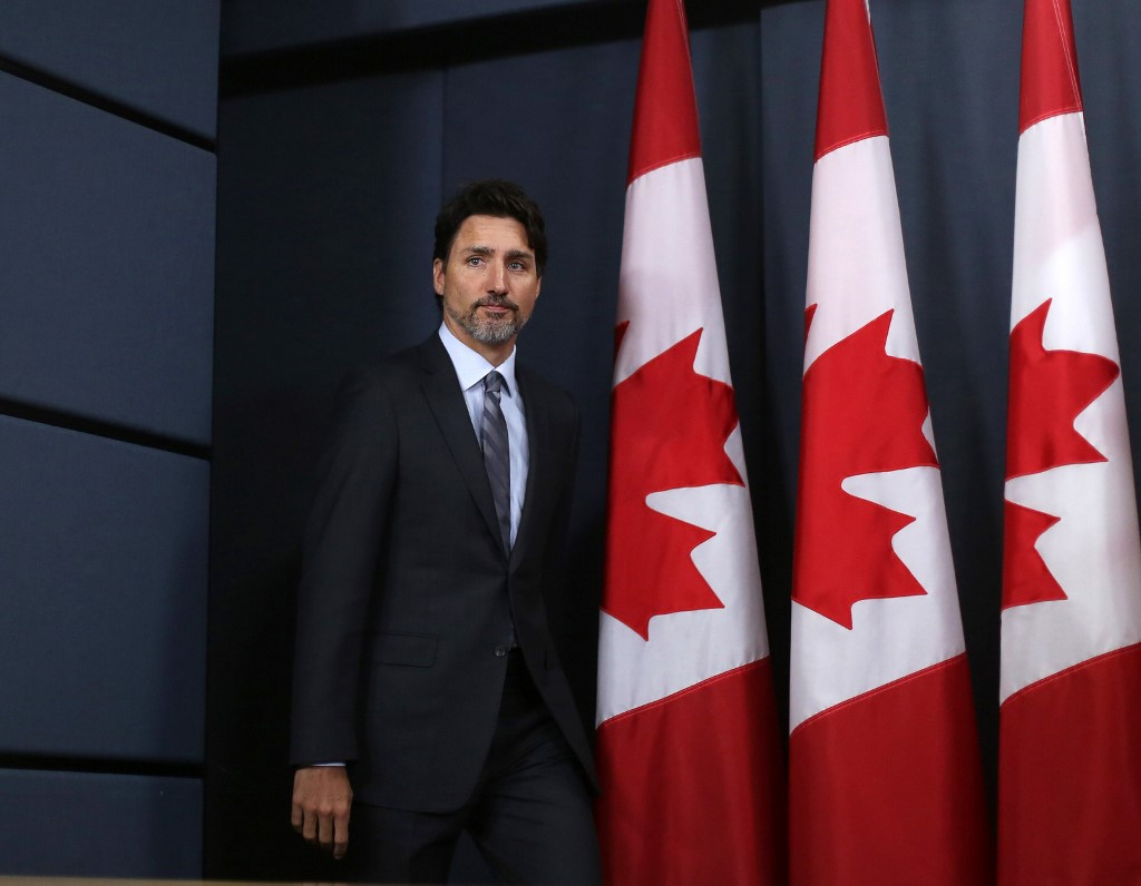 Canadian Prime Minister Justin Trudeau arrives to speak at a news conference in Ottawa on 11 January (AFP)