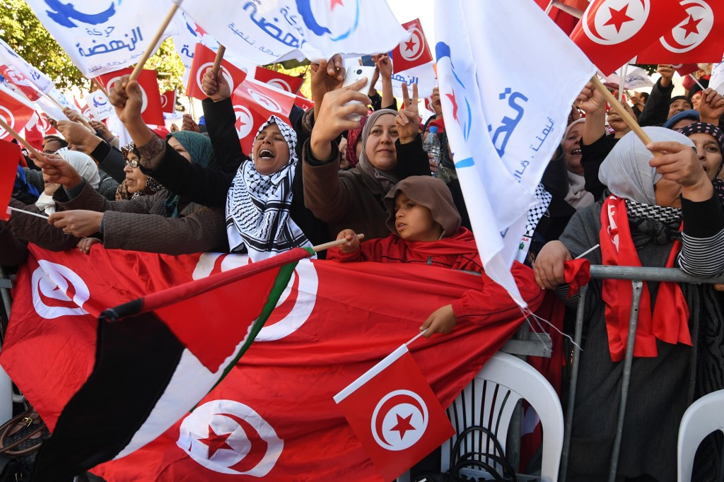 Tunisians wave their national flag and that of Ennahda in Tunis on 14 January 2018 (AFP)