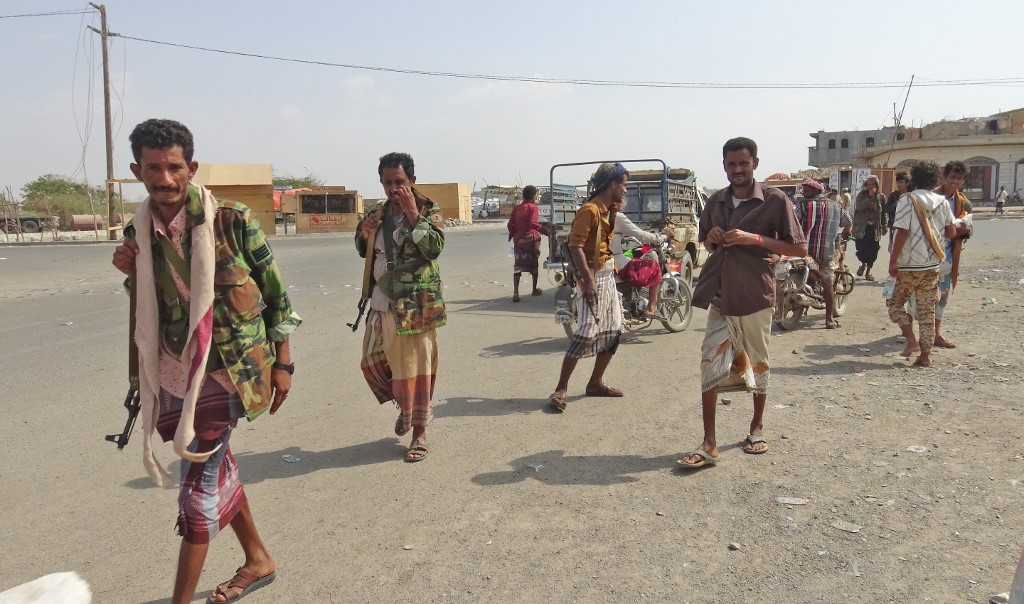 Yemeni fighters loyal to the Saudi-backed president walk down a street in Hodeidah on 18 December (AFP)