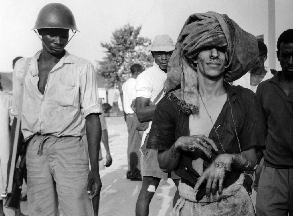 An Arab prisoner led by guards in a camp during the Zanzibar Revolution led by John Gideon Okello, on 12 January 1964. (AFP)